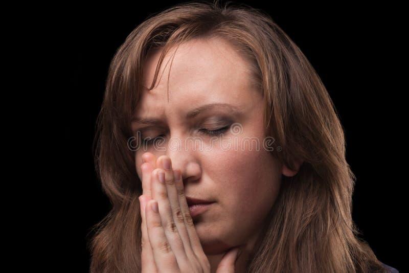 Le jeune femme est dans la prière sur le fond foncé photos stock