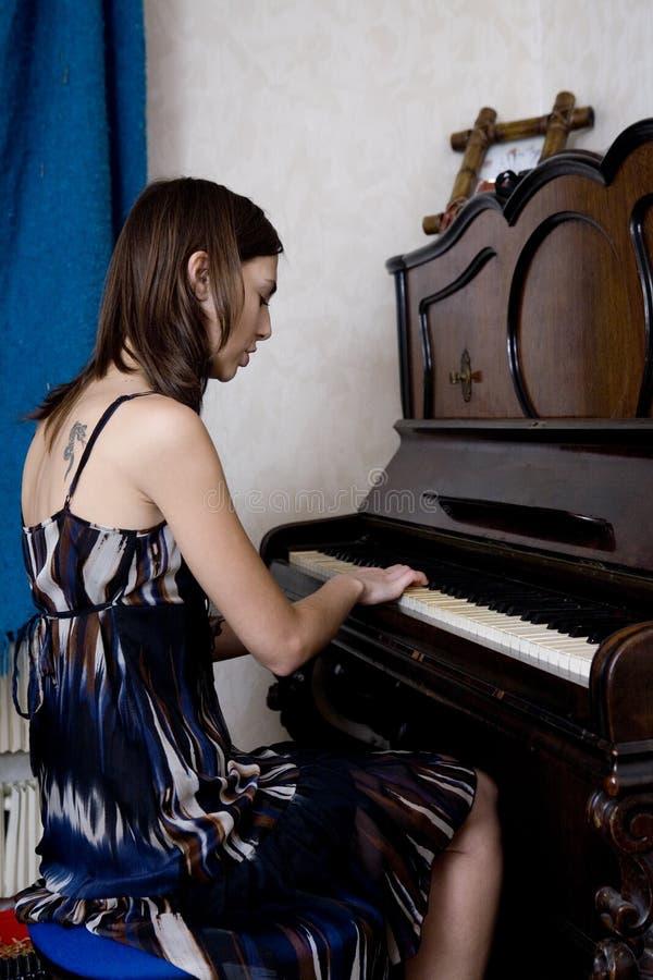 Le jeune femme joue le piano photo stock