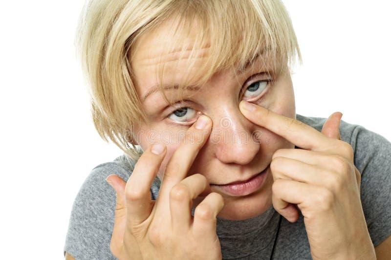 Le jeune femme nettoie des yeux photos stock