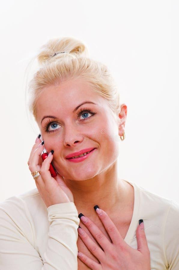 Le jeune femme parle par un téléphone portable photos stock