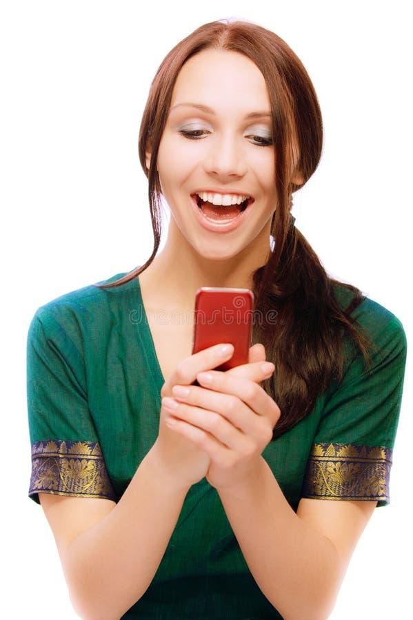 Le jeune femme riant affiche des sms photo stock