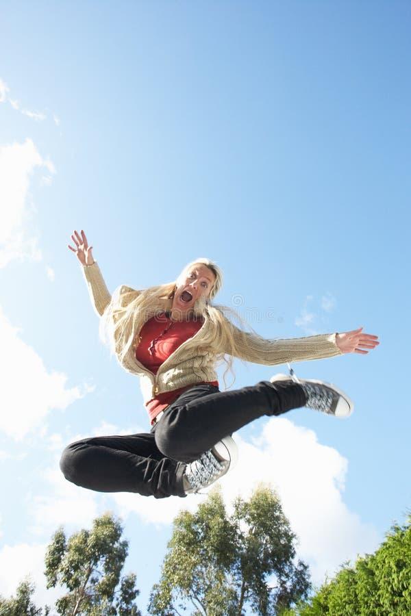 Le jeune femme sautant sur le tremplin a attrapé dans la mi AI photo libre de droits