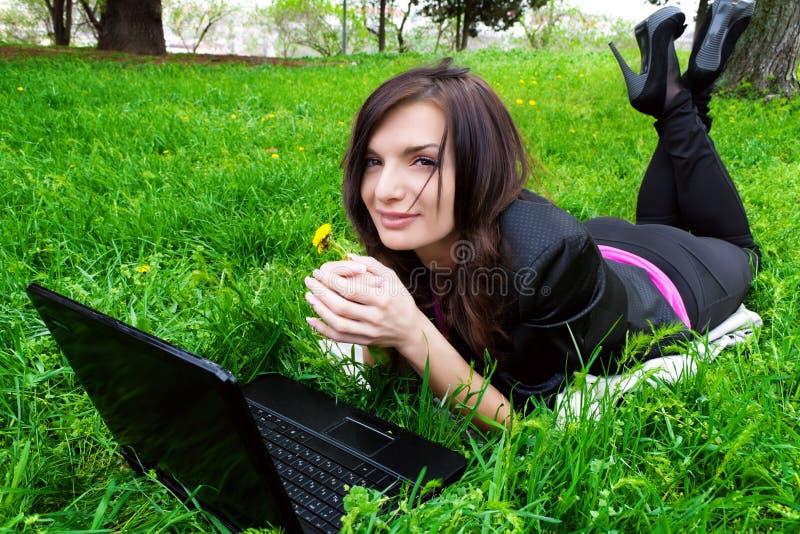 Le jeune femme travaille sur l'ordinateur portatif. image libre de droits
