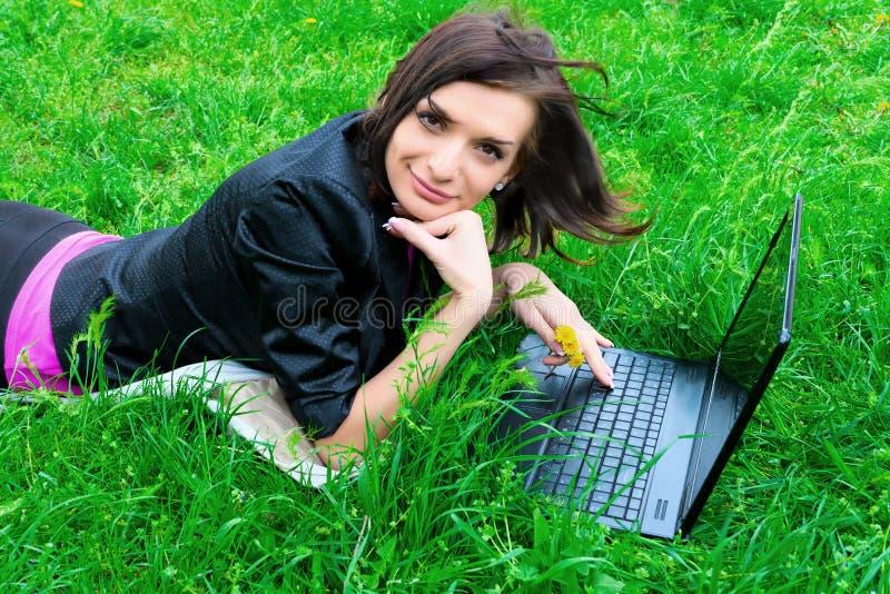 Le jeune femme travaille sur l'ordinateur portatif. photographie stock libre de droits