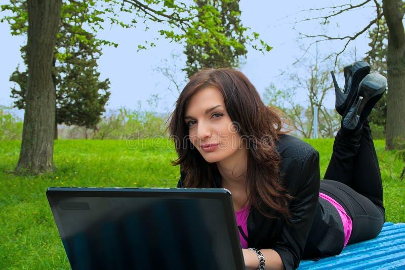 Le jeune femme travaille sur l'ordinateur portatif. images stock