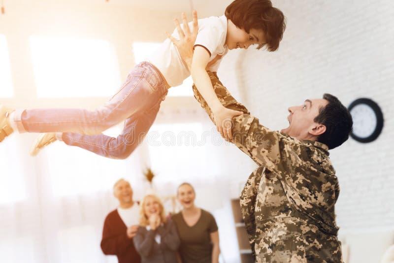 Le jeune fils rencontre un homme dans le camouflage à la maison photo libre de droits