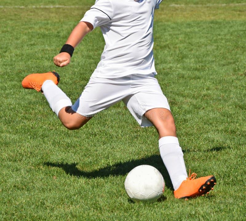 Le jeune footballeur donne un coup de pied la boule photo stock