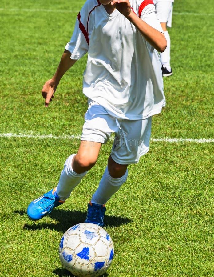 Le jeune footballeur fonctionne avec une boule photos libres de droits