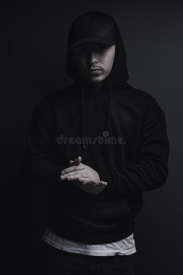 Le jeune frappeur frais avec le hoodie noir et le chapeau battent ses mains devant le fond gris image libre de droits