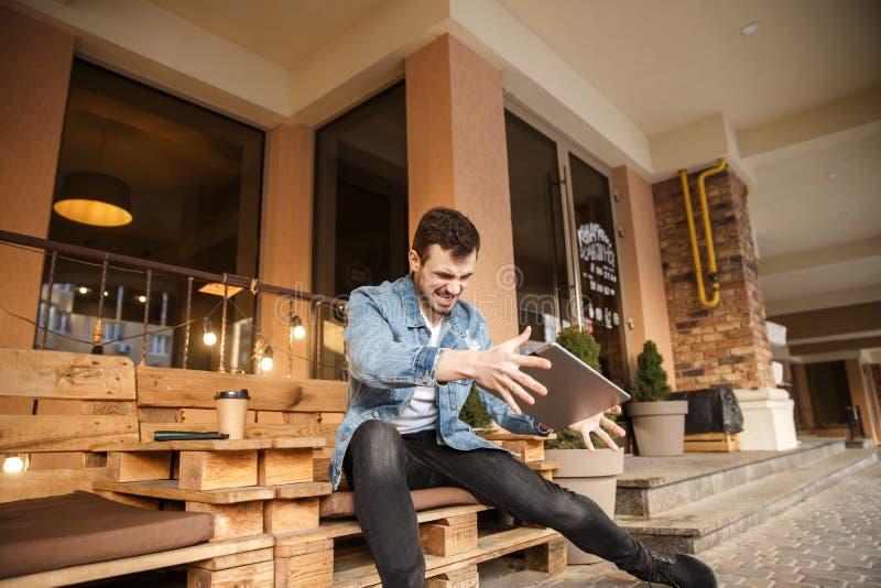 Le jeune gamer furieux va détruire son comprimé Il s'assied sur la terrasse de café Concept de d?faite images stock