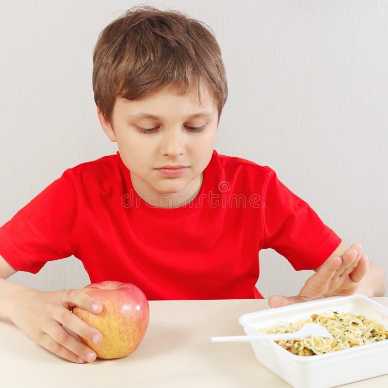 Le jeune garçon à la table choisit entre les nouilles instantanées et la pomme sur le fond blanc photos libres de droits