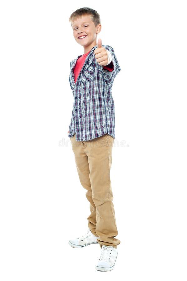 Le jeune garçon affichant des pouces lèvent le geste images stock