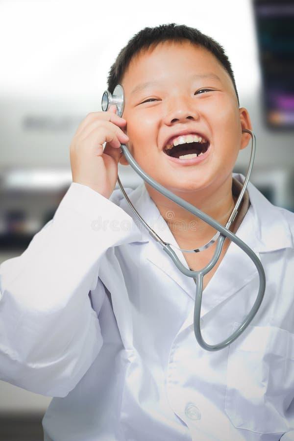 Le jeune garçon asiatique heureux joue un docteur images libres de droits