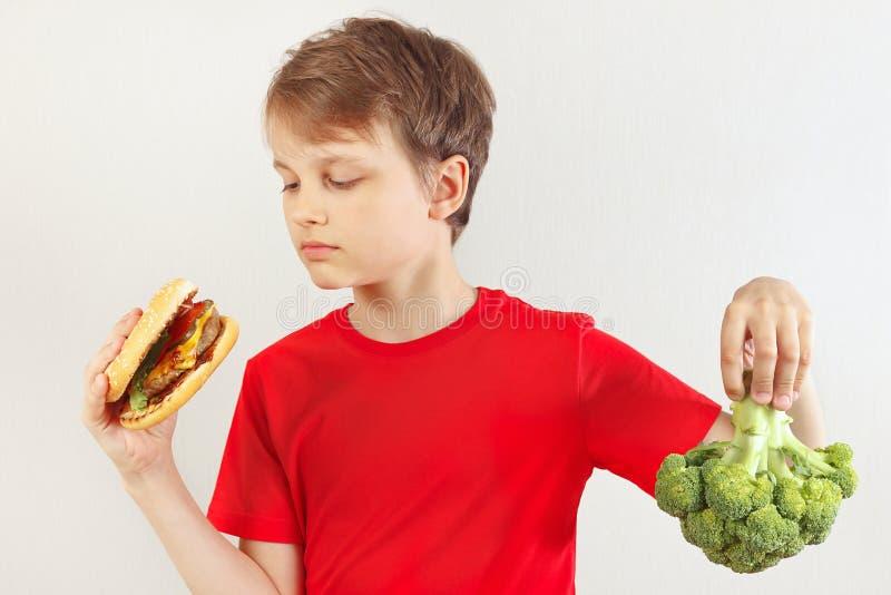 Le jeune garçon choisit entre le prêt-à-manger et le légume sur le fond blanc photographie stock