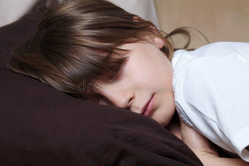 Le jeune garçon dort sur le sofa photographie stock libre de droits