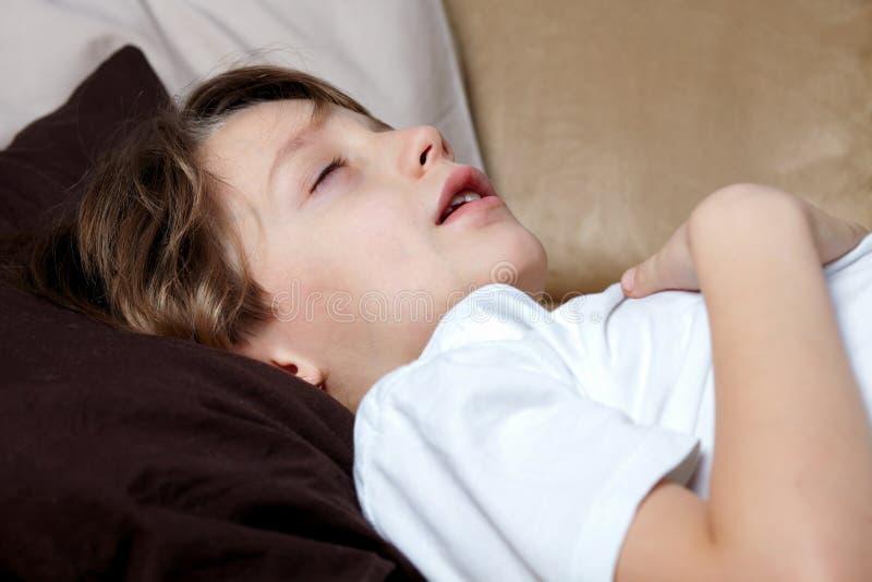 Le jeune garçon dort sur le sofa image stock