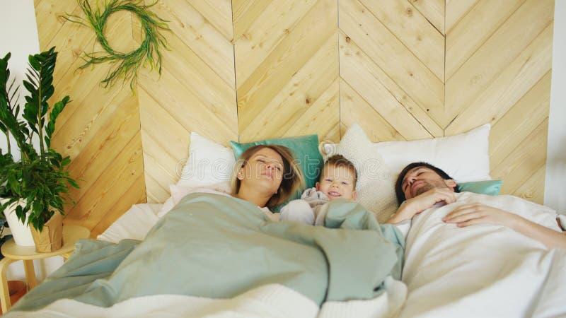 Le jeune garçon drôle se réveillent tandis que ses parents dorment dans le matin sur le lit dans leur maison photographie stock libre de droits