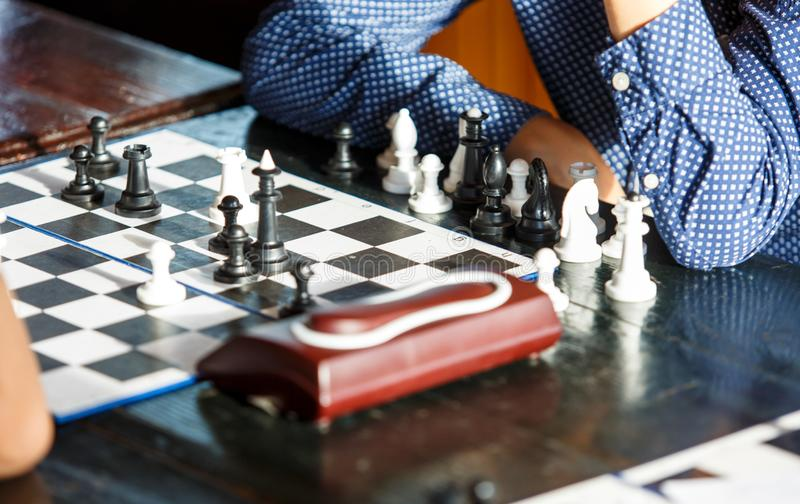 Le jeune garçon futé mignon dans la chemise bleue joue aux échecs sur la formation avant le tournoi colonie de vacances d'échecs  photographie stock