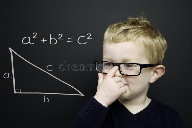 Le jeune garçon intelligent est resté l'infront d'un tableau noir photos stock