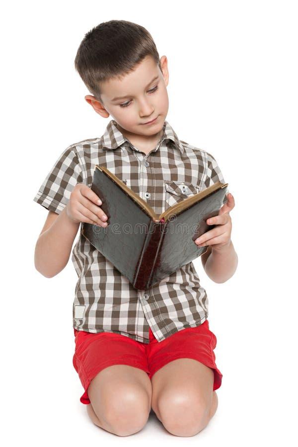 Le jeune garçon lit un vieux livre photos libres de droits