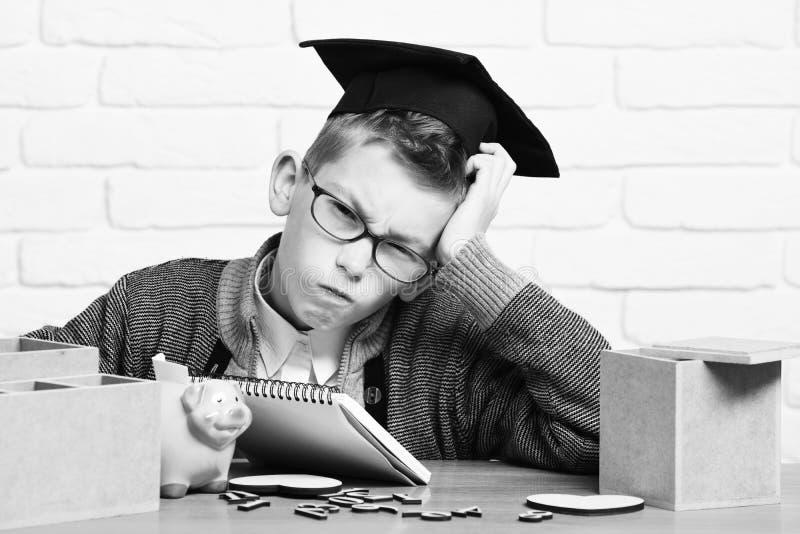 Le jeune garçon mignon d'élève dans le chandail gris et les verres se reposant au bureau avec des nombres en bois communs dentell photographie stock libre de droits