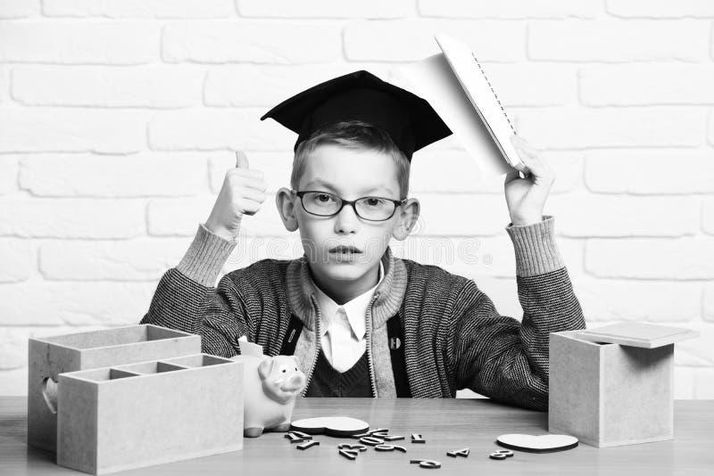 Le jeune garçon mignon d'élève dans le chandail gris et les verres se reposant au bureau avec des nombres en bois de cahier à dis images stock