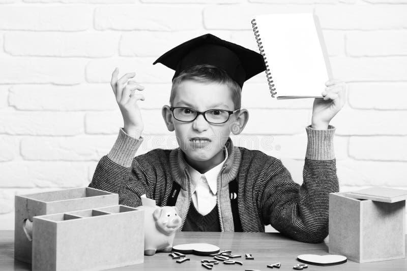 Le jeune garçon mignon d'élève dans le chandail gris et les verres se reposant au bureau avec des nombres en bois de cahier à dis images libres de droits