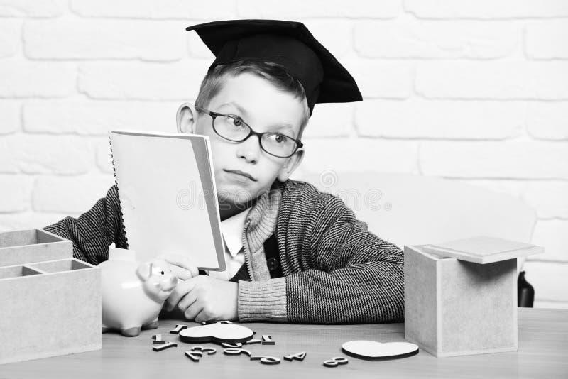 Le jeune garçon mignon d'élève dans le chandail gris et les verres se reposant au bureau avec des nombres en bois de cahier à dis photos libres de droits