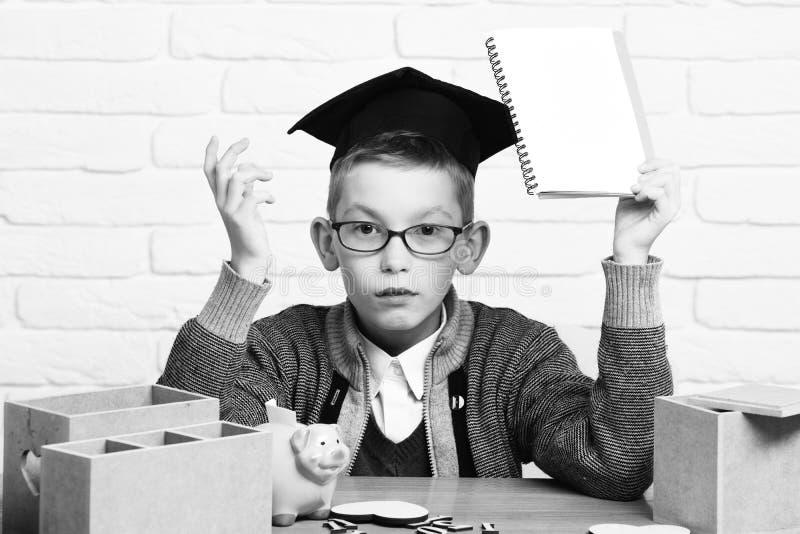Le jeune garçon mignon d'élève dans le chandail gris et les verres se reposant au bureau avec des nombres en bois de cahier à dis image libre de droits