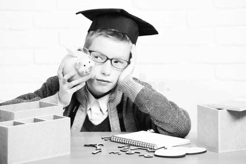 Le jeune garçon mignon d'élève en chandail gris et verres se reposant au bureau a appris en main avec le rose en bois commun de n photographie stock