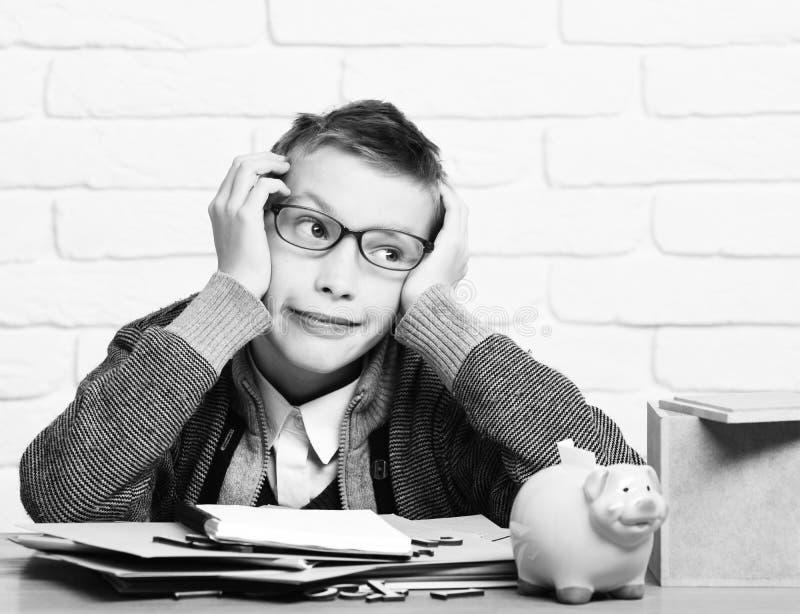 Le jeune garçon mignon d'élève en chandail gris et verres se reposant au bureau s'est penché sur des mains avec la banque porcine photos stock