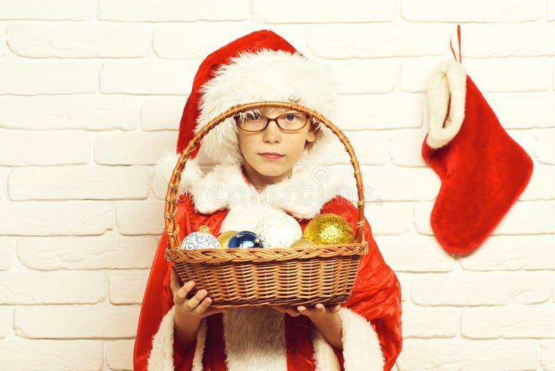 Le jeune garçon mignon du père noël avec des verres dans le chandail rouge et le chapeau de nouvelle année tient Noël décoratif o photographie stock libre de droits