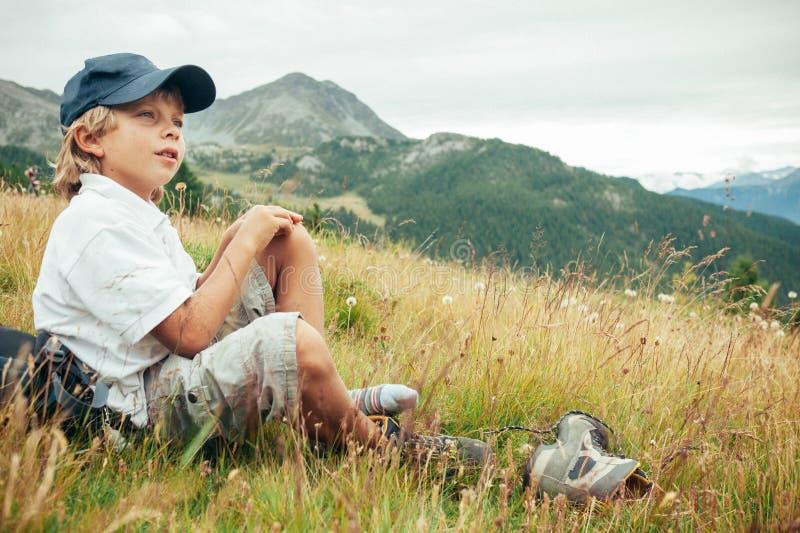 Le jeune garçon prend un repos dans un pré pendant un voyage de montagne images libres de droits