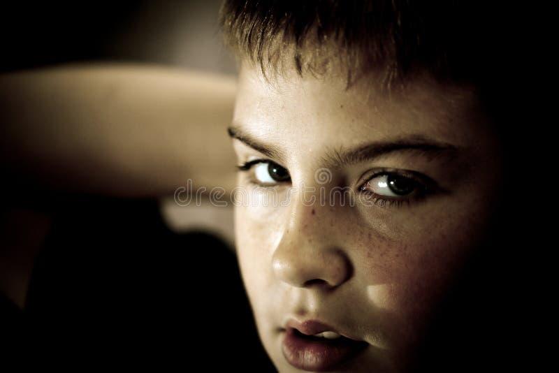 Le jeune garçon recherchant avec espoir dans le sien observe discret image libre de droits