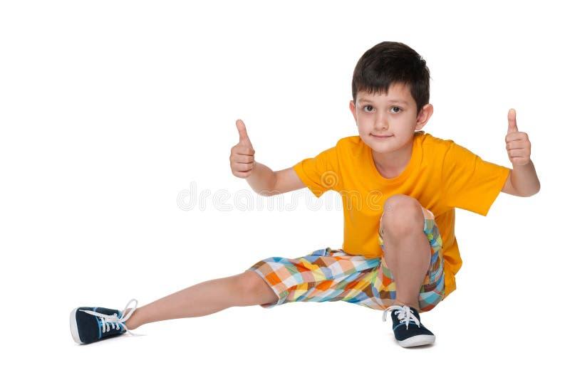 Le jeune garçon repose et tient ses pouces  photographie stock