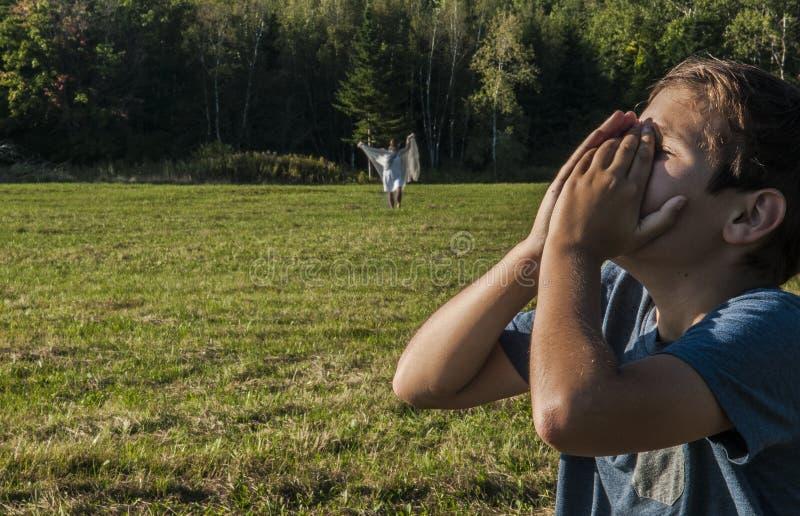 Le jeune garçon s'afflige au-dessus de la vision de sa mère morte photo libre de droits