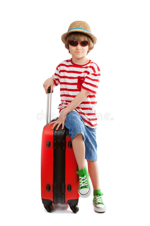 Le jeune garçon s'assied sur la valise rouge photo stock