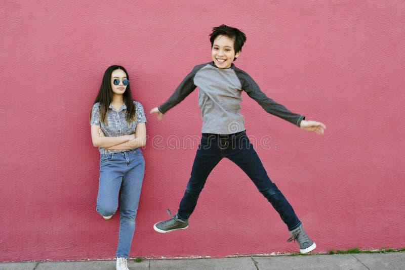 Le jeune garçon saute haut tandis que sa soeur de l'adolescence Watches Unimpressed Energetic image stock