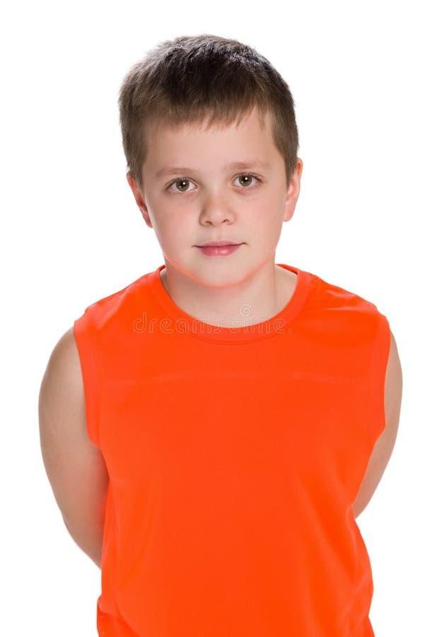 Le jeune garçon se tient sur le fond blanc images stock