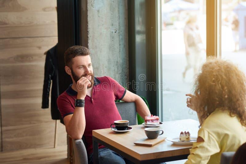 Le jeune garçon semblant adorable sur son amie, café potable, mangeant durcit photographie stock