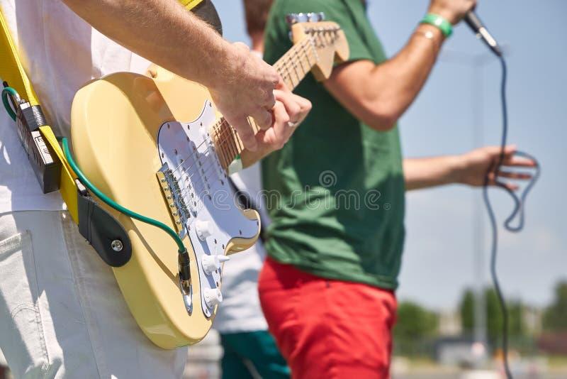 Le jeune groupe de rock exécute leurs chansons sur la rue, plan rapproché image stock