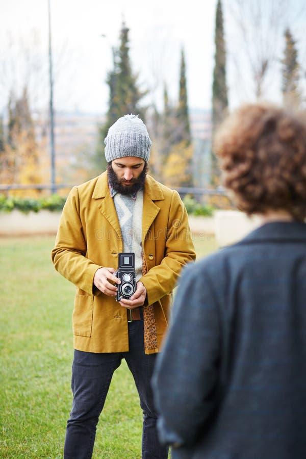 Le jeune hippie barbu prenant la photo à la fille rousse avec TLR est venu image libre de droits