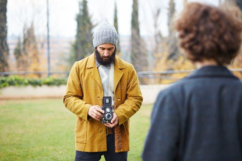 Le jeune hippie barbu prenant la photo à la fille rousse avec TLR est venu photographie stock libre de droits