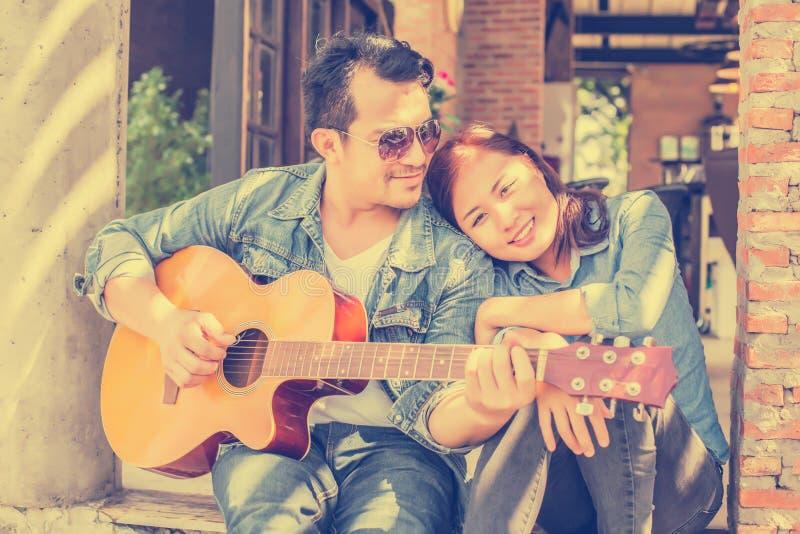 Le jeune hippie a pratiqué la guitare en parc, heureux et a plaisir à jouer la guitare image libre de droits