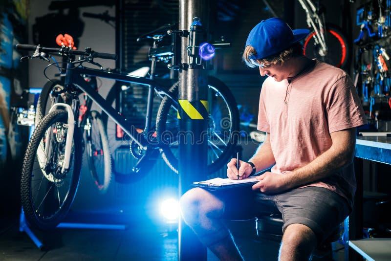 Le jeune homme élégant bel dans un chapeau et avec un petit entrepreneur de tatouage vendant une bicyclette, l'atelier s'assied s image stock