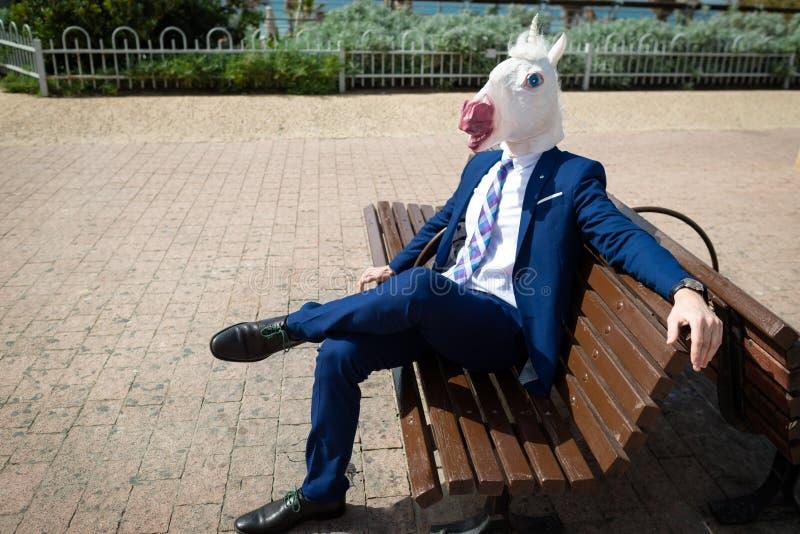 Le jeune homme élégant dans le masque drôle et le costume ont une coupure dans le parc images libres de droits
