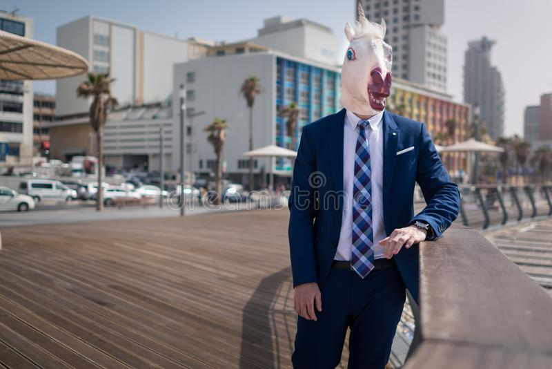 Le jeune homme élégant dans le masque et le costume drôles se tient sur la promenade de ville photo stock