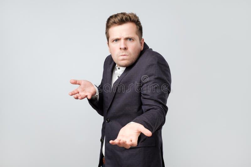 Le jeune homme élégant fâché confus fait des gestes dans la confusion, exprime des émotions négatives photographie stock