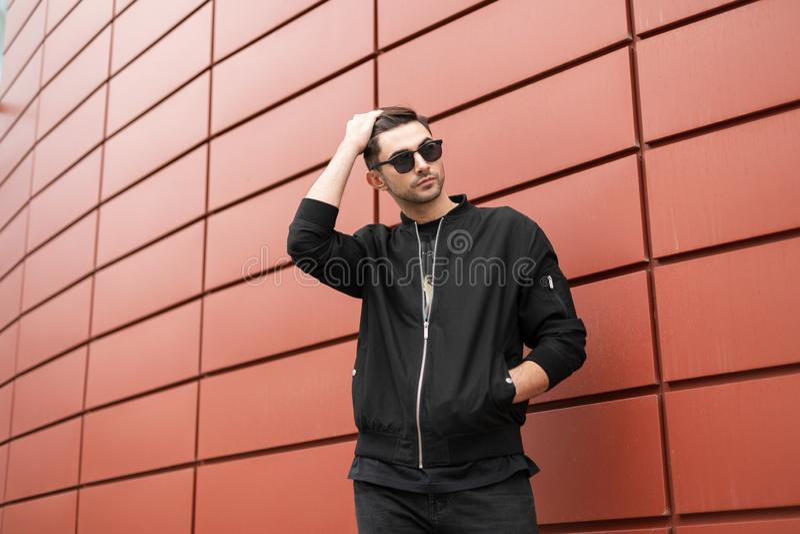 Le jeune homme élégant moderne de hippie dans des vêtements noirs à la mode dans des lunettes de soleil élégantes tient et redres image stock