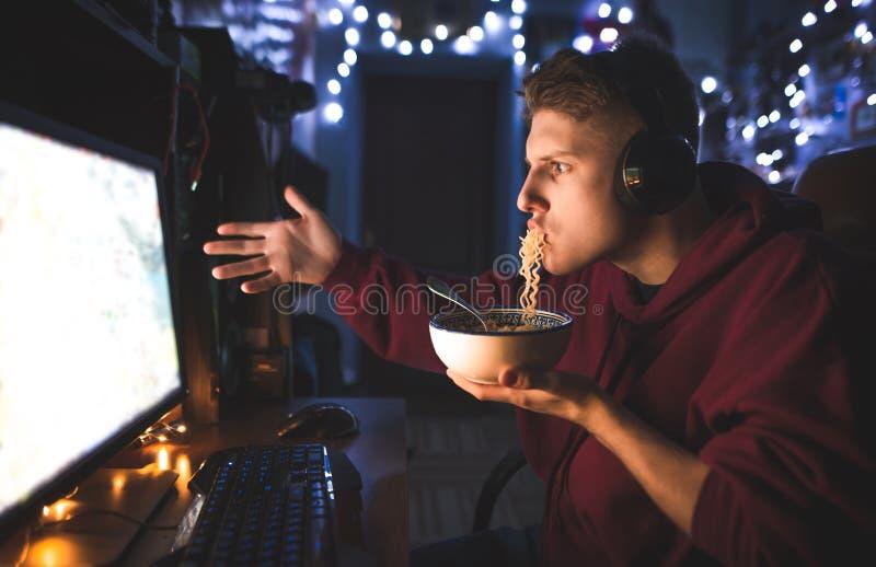 Le jeune homme émotif mange des nouilles à la maison derrière l'ordinateur et les sembler étonné à l'écran image stock